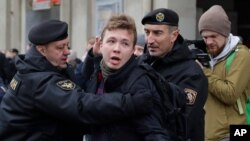 FILE - Belarus police detain reporter Raman Pratasevich, center, in Minsk, March 26, 2017.