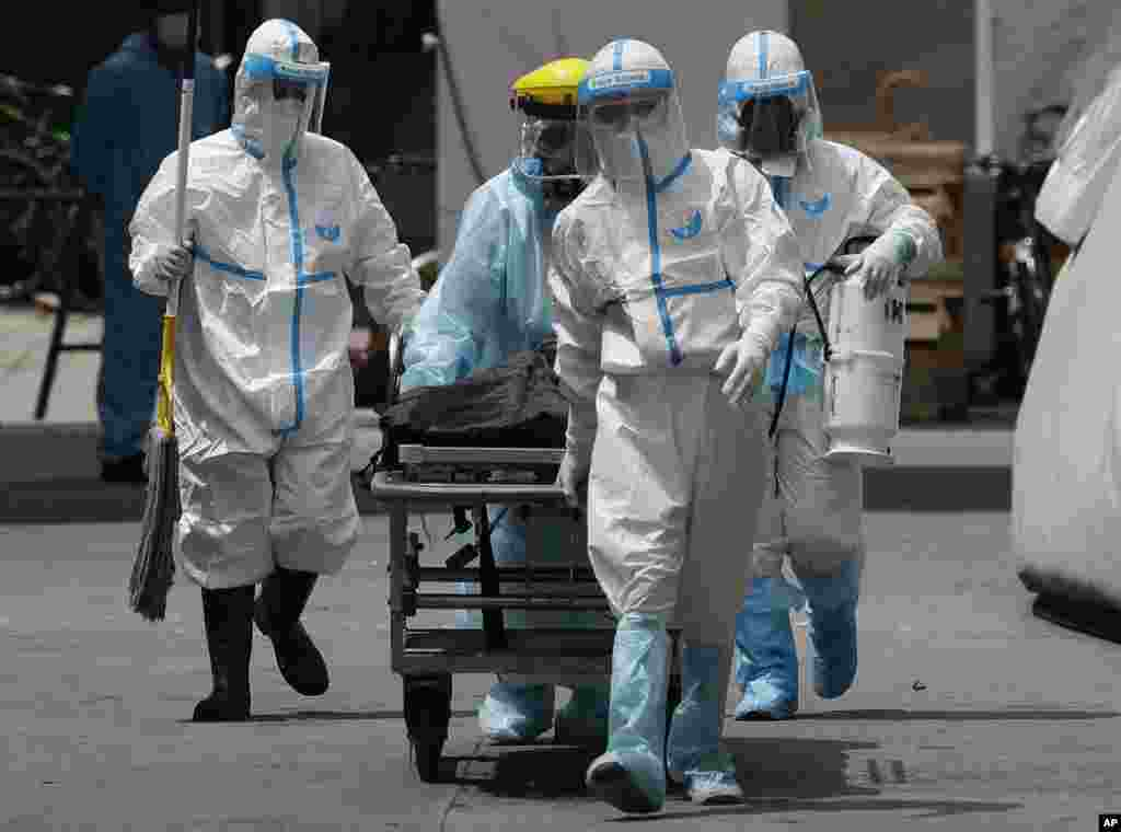 Health workers in protective suits transport a dead body at a hospital in Manila, Philippines. The capital and outlying provinces returned to another lockdown after medical groups warned that the country was waging a losing battle against the coronavirus.