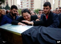 FILE - A relative cries over the coffin of Uygar Coskun, 32, killed in Saturday's bombing attacks, during his funeral, in Ankara, Turkey, Oct. 12, 2015.