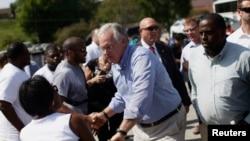 El gobernador de Missouri, Jay Nixon, saluda a manifestantes en Ferguson.