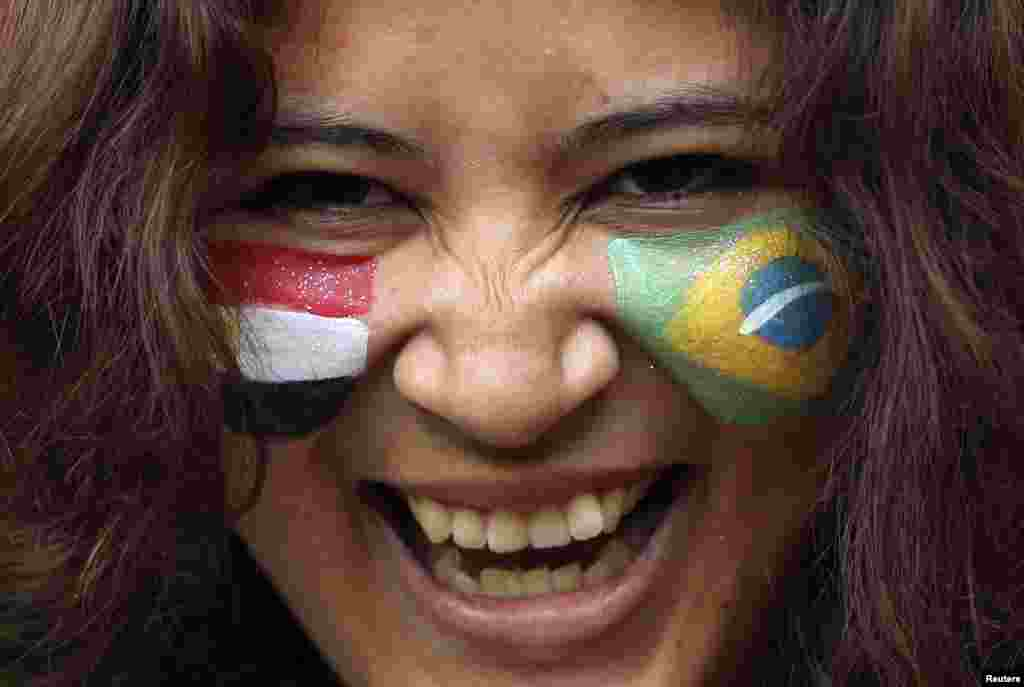 A spectator with a Brazilian and an Egyptian (L) national flag on either cheek smiles ahead of the men's Group C football match between the two countries at the London 2012 Olympic Games in the Millennium Stadium in Cardiff July 26, 2012.