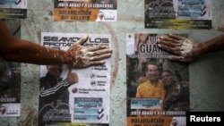 Opposition supporters use their hands to glue posters of candidates for the National Assembly of the Venezuelan coalition from opposition parties (MUD) in Caracas, Dec. 2, 2015.