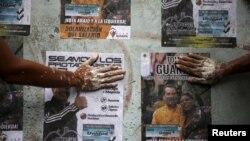 Votantes de oposición pegan pósters de sus candidatos a la Asamblea Nacional en Caracas. Las elecciones legislativas se realizarán el domingo 6 de diciembre.