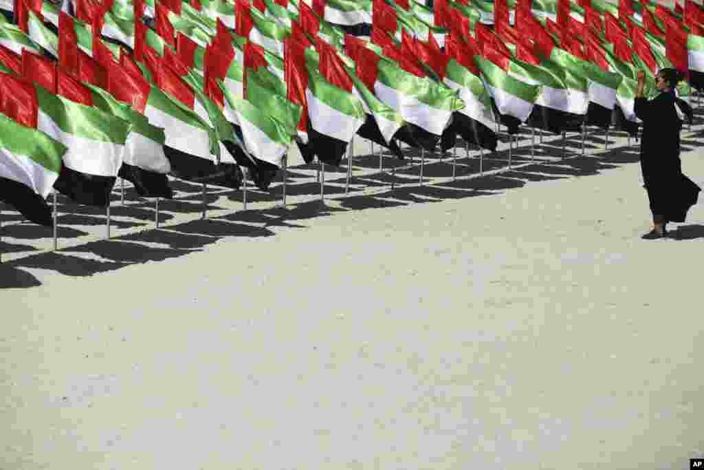 ស្ត្រីម្នាក់ថតរូបនៃការតាំងបង្ហាញទង់ជាតិរបស់កុលសម្ព័ន្ធ Emirati ដែលរៀបចំសម្រាប់ទិវា National Day នៅក្នុងក្រុង Dubai ប្រទេសអេមីរ៉ាតអារ៉ាប់រួម។