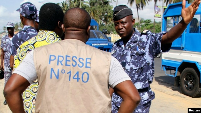 A policeman gestures at a journalist during a sit-in near the presidency to protest against a new media law in Lome, Togo, March 14, 2013.