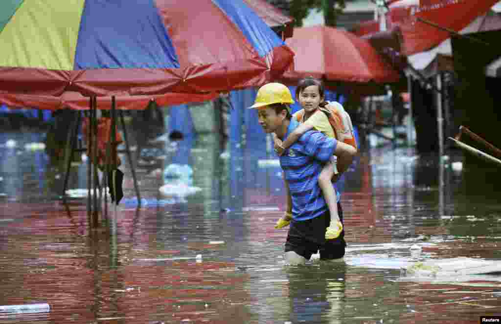 A man carries a girl on his back as he wades through a flooded street after heavy rainfalls hit Changsha, Hunan province, China.