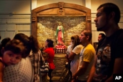 FILE - Worshippers pray next to a shrine to Our Lady of Guadalupe, the patroness of the Americas especially revered by Mexicans, during Mass at the St. John Paul II Pastoral Center in Gainesville, Georgia, Aug. 9, 2015.