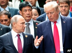 FILE - U.S. President Donald Trump, right, and Russia's President Vladimir Putin talk during the family photo session at the APEC Summit in Danang, Nov. 11, 2017.
