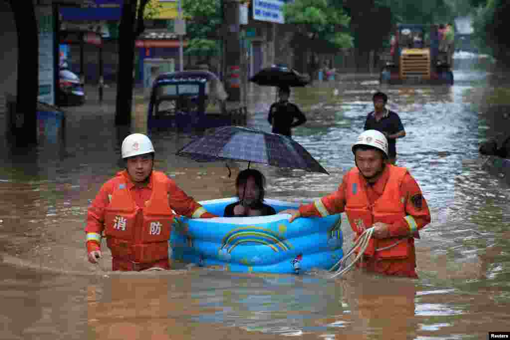Rescue workers evacuate a woman with an inflatable swimming pool on a street following heavy rainfall in Pingxiang, Jiangxi province, China, July 9, 2019.
