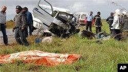 Vítimas de acidente numa estrada moçambicana jazem, cobertos com manta cor de laranja, junto aos destroços dos veículos.