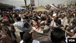Seorang demonstran anti-pemerintah yang tertembak dibawa ke tenda pos kesehatan di tengah bentrokan dengan pasukan keamanan di Sana'a, Jumat (18/3).
