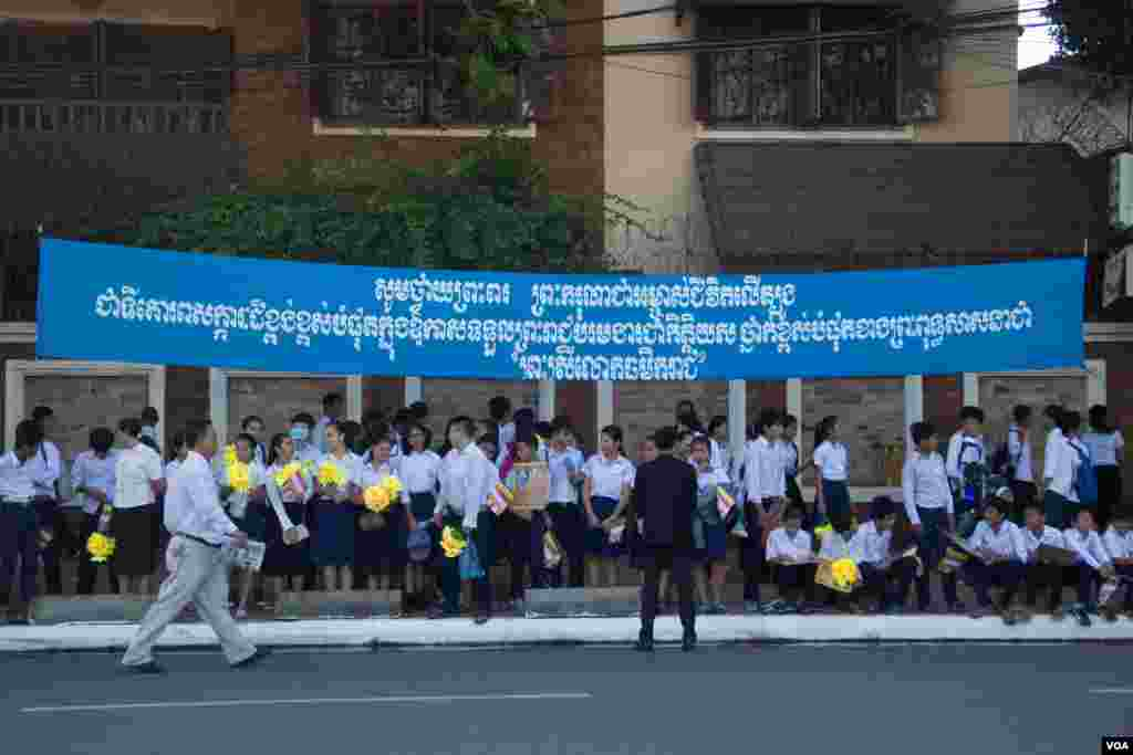 "Students are waiting on the pavement under the banner with text honoring the title ""Preah Sri Loka Dhammika Raja"" to King Norodom Sihamoni on June 3, 2015. (Nov Povleakhena/VOA Khmer)"