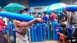 A man carries an oxygen tank as he walks past people waiting with oxygen tanks in need of refill outside the Naing oxygen factory at the South Dagon industrial zone in Yangon, Myanmar, Wednesday, July 28, 2021. Myanmar is currently reeling from…