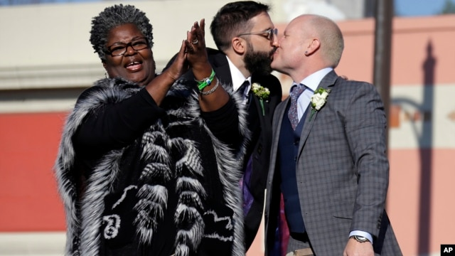 Aubrey Loots (R) and Danny Leclair, the first gay couple to be married aboard a float in the Tournament of Roses, kiss after being wed by the Rev. Alfreda Lanoix of the Unity Fellowship Church of Christ (L), aboard the AIDS Healthcare Foundation float in