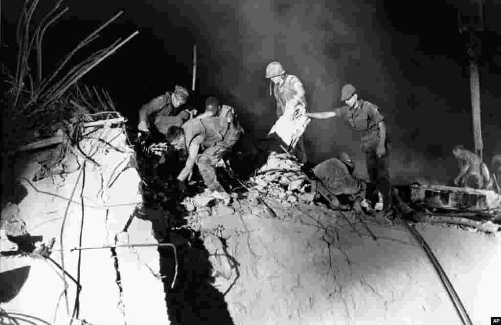 FILE - U.S. Marines and an Italian soldier, right, dig through the rubble of the the U.S. Marine barracks in Beirut, Lebanon, Oct. 23, 1983.