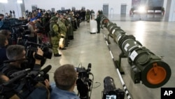FILE - Foreign military attaches and journalists attend a briefing by the Russian Defense Ministry as a land-based cruise missile, right, is displayed in Kubinka outside Moscow, Russia, Jan. 23, 2019. The Russian military said the new weapon does not violate the INF Treaty.