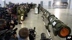 Foreign military attaches and journalists attend a briefing by the Russian Defense Ministry as the 9M729 land-based cruise missile, right, in Kubinka, Russia, Jan. 23, 2019.
