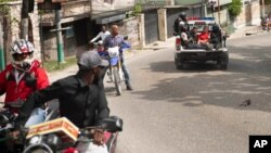 A police truck takes two suspects to the police station of Petion Ville in Port-au-Prince, Haiti, Thursday, July 8, 2021. Police Chief Leon Charles said the two are suspects in the assassination of Haitian President Jovenel Moïse.