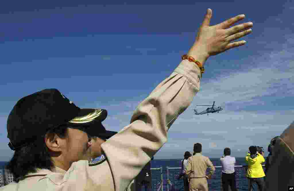 An officer flashes hand signals to a passing helicopter from the stern of a Taiwanese Kidd-class destroyer during exercises off the southern city of Kaohsiung,Taiwan, May 16, 2013.