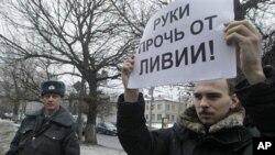"""Jedan protu-vladin aktivist iz oporbene skupine Lijevi front, drži parolu """"Dižite ruke od Libije"""" u Moskvi, 19. ožujka 2011."""