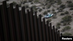 A U.S. police patrol vehicle is seen behind a section of the wall separating Mexico and the United States, on the outskirts of Ciudad Juarez, Mexico, Nov. 12, 2016.