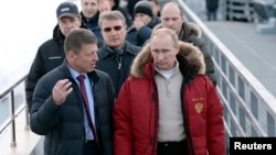 Russian President Vladimir Putin (R), Sberbank President German Gref (C) and Deputy Prime Minister Dmitry Kosak visit an Olympic venue near Sochi, Jan. 3, 2014.