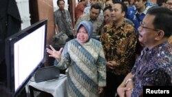 Walikota Surabaya Tri Rismaharini menunjukkan cara mengakses perizinan lewat Internet kepada ORI Jatim dan pengusaha. (VOA/Petrus Riski)