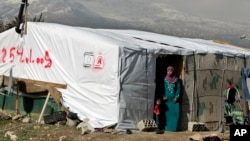 FILE - A Syrian refugee stands outside her tent in a refugee camp in the eastern town of Houch al-Harimeh, Lebanon.