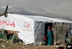 Người tị nạn Syria đứng bên ngoài căn lều trong trại tị nạn ở thị trấn phía đông Houch al-Harimeh ở Libăng.