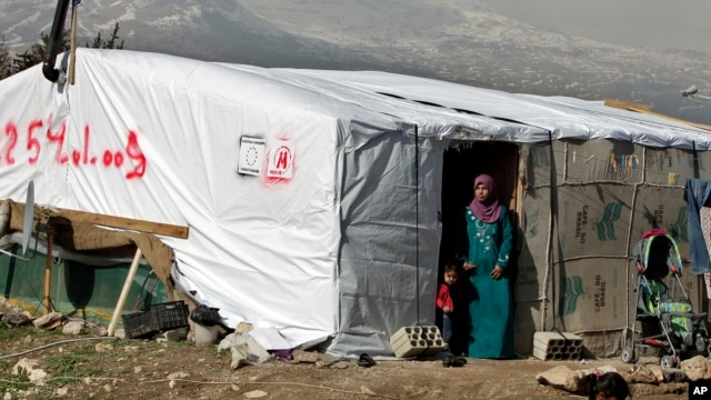 FILE - A woman stands outside her tent in a Syrian refugee camp in Houch al-Harimeh, Lebanon. Refugees in Syria's neighboring countries often live in terrible conditions, spurring many to attempt the journey to Europe.