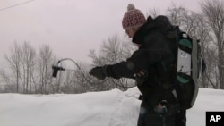 An image taken from video shows Patrick Alexander, a postdoctoral researcher at Columbia University's Lamont-Doherty Earth Observatory, using a spectrometer to measure light radiating off a snowpack in Highmount, N.Y., March 9, 2018.