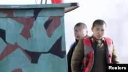 지난 10일 북한 신의주 인근 압록강에서 순찰정에 탄 북한 군인들이 중국 쪽을 바라보고 있다. 중국 단둥에서 촬영한 사진이다. (자료사진)