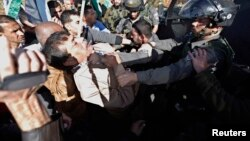 Palestinian minister Ziad Abu Ein (L) scuffles with an Israeli border policeman near the West Bank city of Ramallah, Dec. 10, 2014.