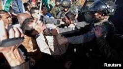 Menteri Palestina Ziad Abu Ein (kiri) saat bentrok dengan polisi Israel di dekat Ramallah, Tepi Barat Rabu (10/12).