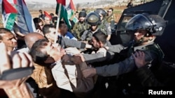 Palestinian minister Ziad Abu Ein (L) scuffles with an Israeli border policeman near the West Bank city of Ramallah, Dec. 10, 2014.