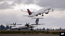FILE - A Delta jet takes off in view of an Alaska Airlines plane that just landed at Seattle-Tacoma International Airport in Washington, Dec. 16, 2015.