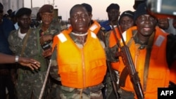 Guinea Bissau soldiers escort Captain Pansau N'Tchama (C), accused of being the mastermind behind the October 21 attack on an elite army barracks, shortly after his arrest in Bolama, on October 27, 2012.