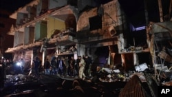 People gather in the aftermath of a multiple explosive attack in the Sayyida Zeinab area, 10 kilometers south of Damascus, Syria, Feb. 21, 2016. The Islamic State group claimed responsibility for a triple blast in the Shi'ite suburb. (AP Photo/Natalia Sancha)