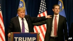 Republican presidential candidate Donald Trump, left, puts his hand on the shoulder of his son, Eric, while speaking after his caucus victory in Nevada, Feb. 23, 2016 in Las Vegas. (AP Photo/Jae C. Hong)