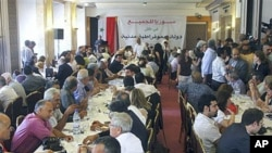Prominent opposition figures and critics of Syrian President Bashar al-Assad's regime gather for a meeting, with attached banner in Arabic that reads 'Syria is for everybody, in the shadow of a democratic civil state,' in Damascus, Syria, June 27, 2011