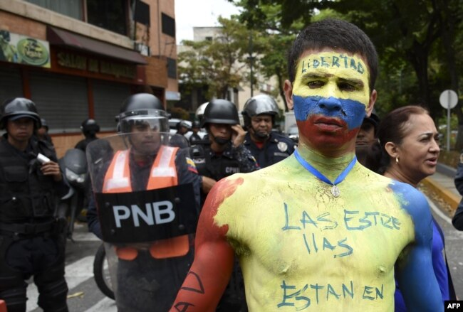 A man with his body painted in the Venezuelan national flag's colors demonstrates in front of riot police during an opposition demonstration calling for the armed forces to disobey Venezuelan President Nicolas Maduro, near La Carlota Air Base in Caracas, May 4, 2019.