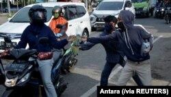 Para pedagang kaki lima menawarkan sarung tangan kepada para pengendara motor di sebuah pos pemeriksaan di tengah pemberlakuan Pembatasan Sosial Berskala Besar untuk mencegah penyebaran virus corona (Covid-19) di Makassar, Sulawesi Selatan, 6 Mei 2020. (F