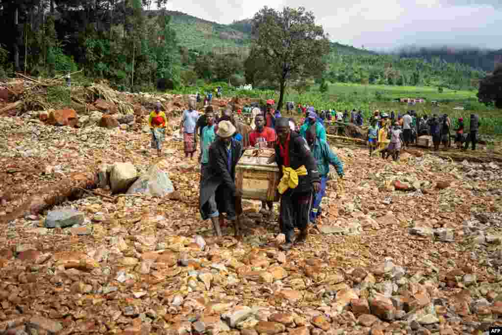 Men carry a coffin along a temporary path on the river in Ngangu township Chimanimani, Manicaland Province, eastern Zimbabwe, after the area was hit by Cyclone Idai.