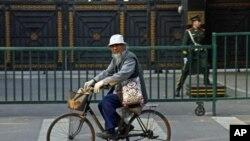 中国政府推出行政命令,削减工业落后产能,其中钢铁产能削减幅度最大。图为一名男子骑自行车穿过北京街头。