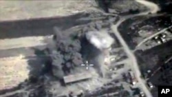 In this photo made from the footage taken from Russian Defense Ministry official web site on Sunday, Oct. 4, 2015, an aerial view of a bomb explosion in Syria.