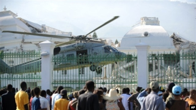 Haitians watch as a US Navy helicopter lands in front of the heavily damaged presidential palace in Port-au-Prince 19 Jan 2010
