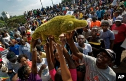 "FILE: Supporters of Zimbabwe's President in waiting Emmerson Mnangagwa, known as ""The Crocodile"", raise a stuffed crocodile in the air as they await his arrival at the Zanu-PF party headquarters in Harare, Zimbabwe, Nov. 22, 2017."