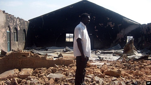 A file picture taken on January 24, 2010, shows a Christian resident of the Nigerian city of Jos standing near a church burnt in ongoing sectarian violence.