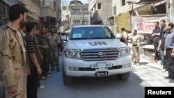 Binh sĩ thuộc Quân đội Syria Tự do vây quanh đoàn xe của các thanh sát viên LHQ đến điều tra về vấn đề vũ khí hóa học ở ngoại ô Zamalka, ngày 28/8/2013.