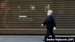 Starija žena, sa maskom na licu, hoda centrom Beograda, tokom vanrednog stanja, 21. aprila 2020. (AP Photo/Darko Vojinović)